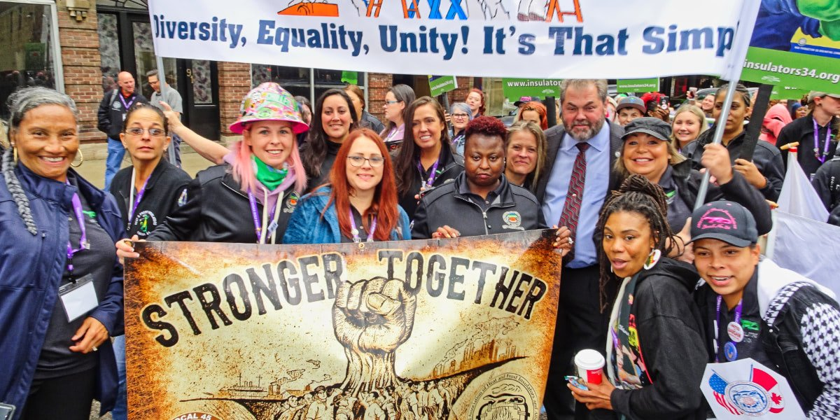 Group photo of female construction workers at the Women Build Nation conference holding a Stronger Together banner